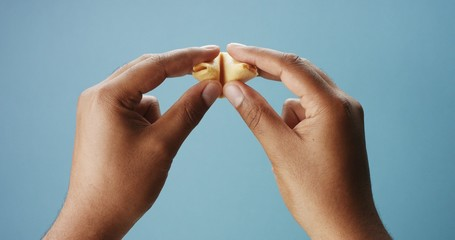 mixed race man's hand open a fortune cookies with an empty paper