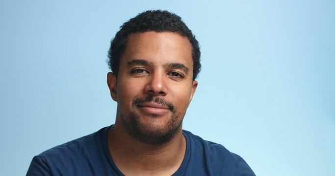 sleepy mixed race man portrait on a deep blue background