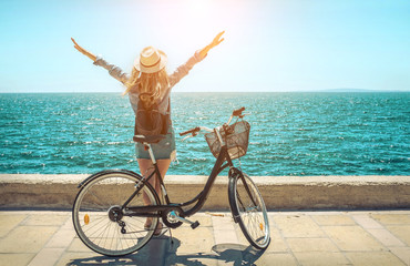 Blonde woman in summer hat with her bicycle walking coastline by
