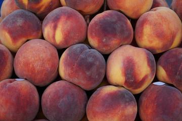 Piles of seasonal fresh sweet juicy gradient color peach background in local city fruit market