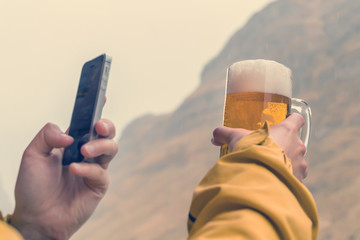 Man in a yellow jacket takes a beer mug on his phone