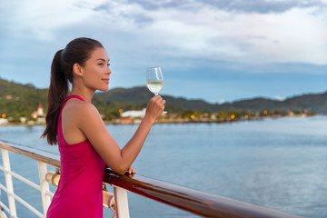 Wall Mural - Luxury cruise ship vacation elegant woman drinking glass of champagne at dinner enjoying ocean view from boat. Asian lady in red dress relaxing on deck outdoor.