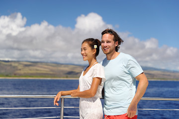 Wall Mural - Cruise vacation happy couple relaxing on yacht in Hawaii. Young people having fun on scenic boat tour in Kauai, ocean tourism activity. Asian woman, Caucasian man.