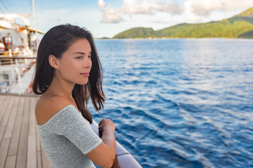 Wall Mural - Cruise ship luxury vacation travel woman boat passenger looking at sunset from deck. Beautiful Asian girl tourist relaxing outside enjoying view.