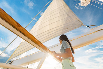 Wall Mural - Luxury cruise ship vacation woman on yacht deck at sunset. Travel in Tahiti sail and mast on sky. Boat passenger sailing away on tropical getaway traveling in French Polynesia.
