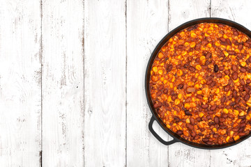 Hot chili con carne in a cast iron pan on light wooden background, top view