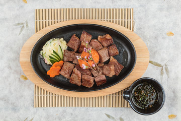 Top view of Garlic Saikoro Steak: medium rare dice wagyu topping with mince carrot on hot plate served with potato salad with ponzu sauce on wooden plate on makisu (meal mat).