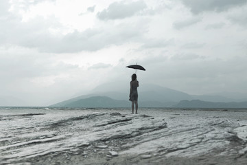 woman with black umbrella looks at infinity in a surreal scene