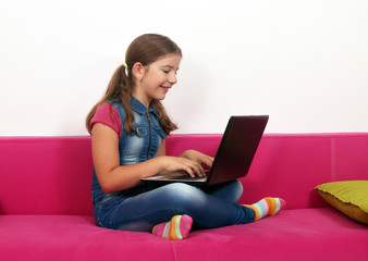 Happy little girl sitting on bed and playing laptop at home