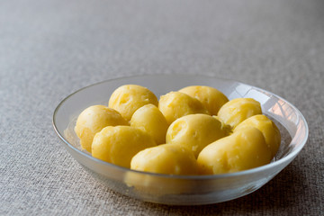 Boiled Potatoes in glass bowl on grey surface.