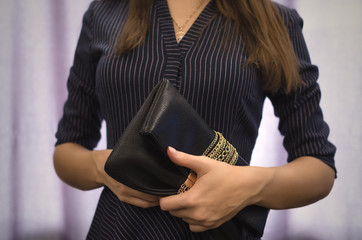 Young woman in dark dress with black leather clutch bag in her hands. Shopping.