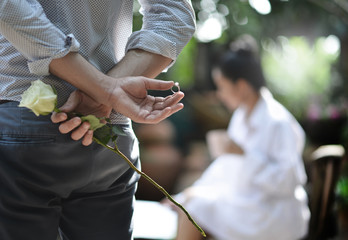 A man holding a ring and rose behind him about to give and propose to a woman