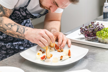 The chef is garnishing appetizer dish
