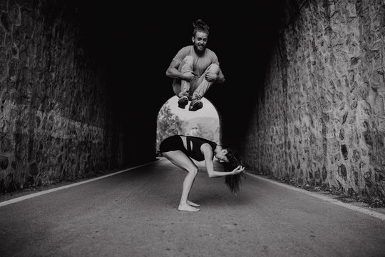 Smiling man jumping over his girlfriend while playing on a road., black and white