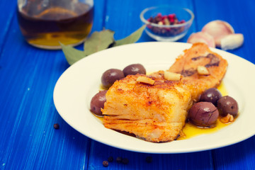 fried cod fish with garlic and olive oil on dish