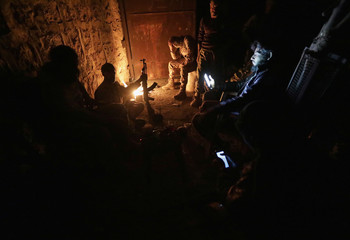 Free Syrian Army fighters warm themselves around a fire in the town of Tadef in Aleppo province