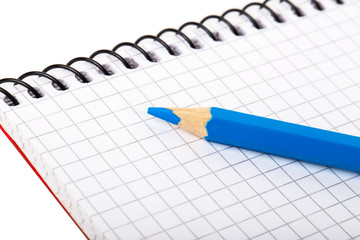 blank notebook and blue pencil