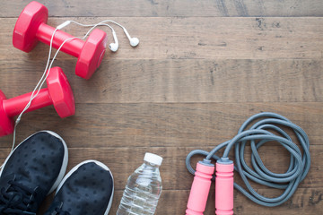 Red dumbbells, sport shoes, bottle of water and jumping rope on wood background with copy space