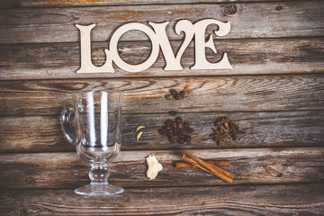 Empty glass for mulled wine and spices for making a drink and inscription love