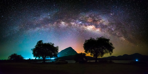 Panoramic milky way galaxy with foreground of mountain, colorful city light and silhouette trees at Lam Isu Reservoir, Kanchanaburi province, Thailand. Long exposure, low light.