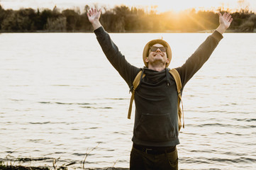 Happy traveller man raising arms to the sky in sign of freedom