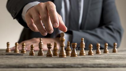 Businessman wearing business suit reaching dark King chess piece