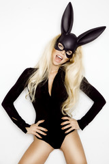 Sexy woman with large breasts, wearing a black mask Easter bunny, standing on a white background and looks very sensually