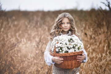 A little girl is standing on the field and holding a wicker basket with wildflowers.  The child has typed a full basket of flowers and smiles.