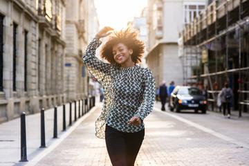 Cheerful ethnic woman walking at street