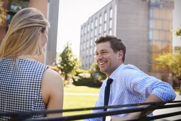 Businessman Talking To Female Colleague On Break In Park