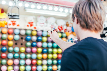 Young man aims at wall of colourful air baloons in order to win teddy bear or plush toy prize for his girlfriend, during romantic date at amusement park or carnival
