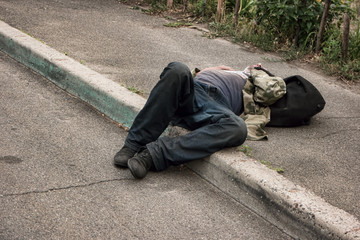 Unconscious drunk man. Person lying in the street. Health problems of the homeless.