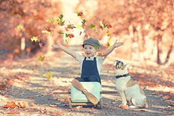 Herbst - Junge spielt mit seinem Hund im Park