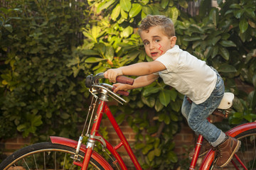 Portrait child dressed as a rocker driving a big red vintage bycicle