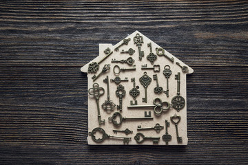 Handmade home symbol with vintage keys on wooden background.