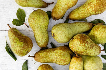 Abate fetel pears with leaves on white painted wood from above.