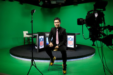 Chinese commentator Wang Zixing poses for a picture after broadcasting a live commentary of a NFL American football game in a studio of the media and gaming firm Tencent Holdings in Beijing