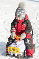 Little boy in red outfit playing happily over the snow