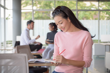 Asian businesswoman writes on a document in startup office