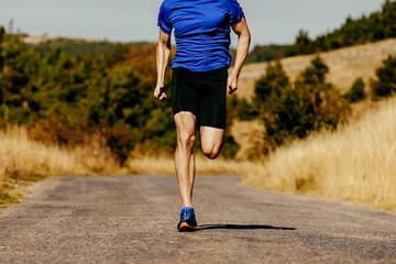 Fotomurales - muscular legs men runner running on asphalt road in autumn field