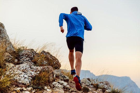 back runner man athlete running uphill trail over stones