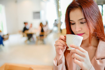 Portrait of beautiful woman holding a cup of coffee in her hand on blur background coffee shop, she drink coffee in the morning