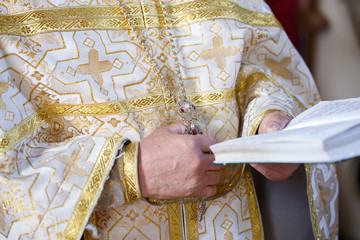 priest holding the Holy Bible with a red ribbon on the wedding ceremony