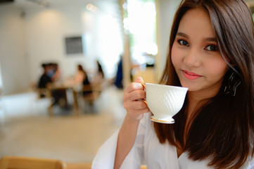 Portrait of beautiful woman holding a cup of coffee in her hand in blur background coffee shop, she drink coffee in the morning