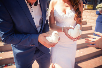 Wedding couple holding white doves