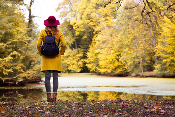 Beautiful woman tourist with backpack in park. Young girl standing over lake in autumn season.