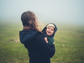 Woman with baby on moor in the fog