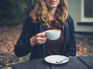 Young woman drinking coffee outside in autumn