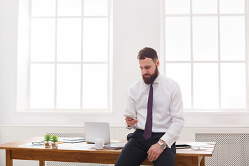 Pensive  businessman using cell phone in white modern office