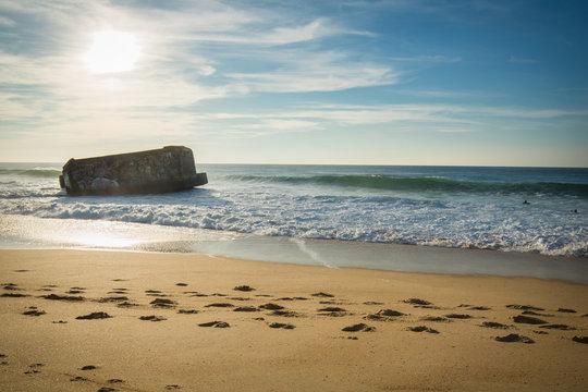 silhouette of war blockhouse on scenic beautiful sandy beach seascape with waves on atlantic ocean in blue sky in capbreton, france